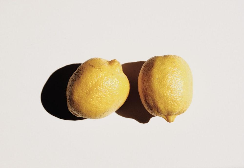 2 yellow lemon fruits on white surface