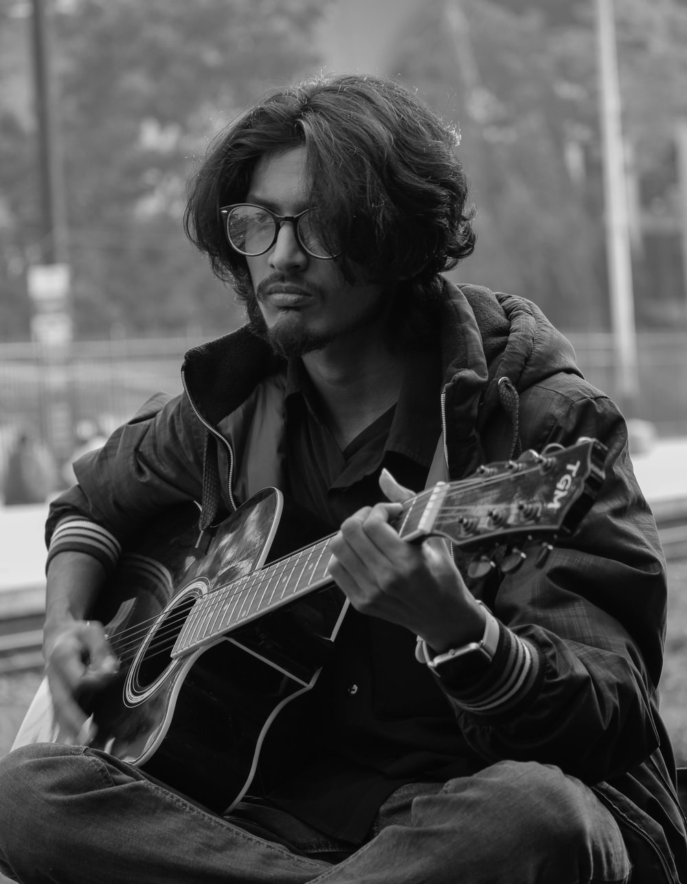 man playing acoustic guitar in grayscale