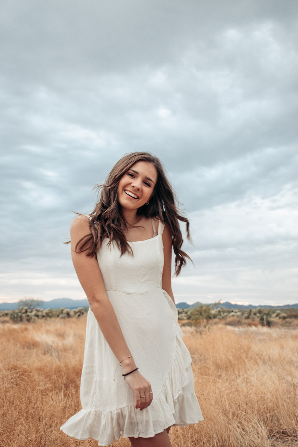 woman in white sleeveless dress standing on brown grass field during daytime
