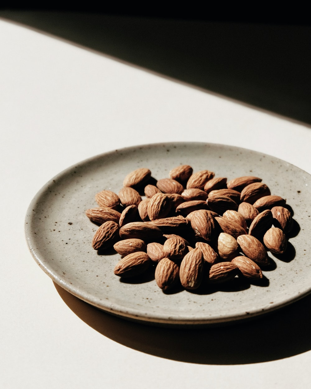 brown coffee beans on white ceramic bowl