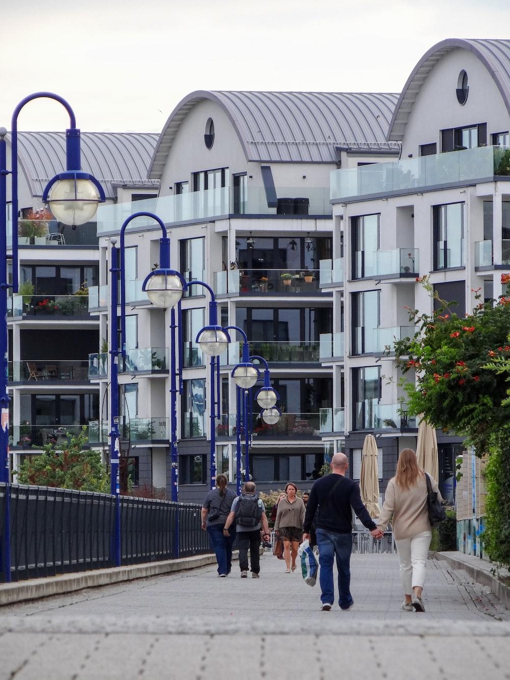 people walking on sidewalk near white building during daytime