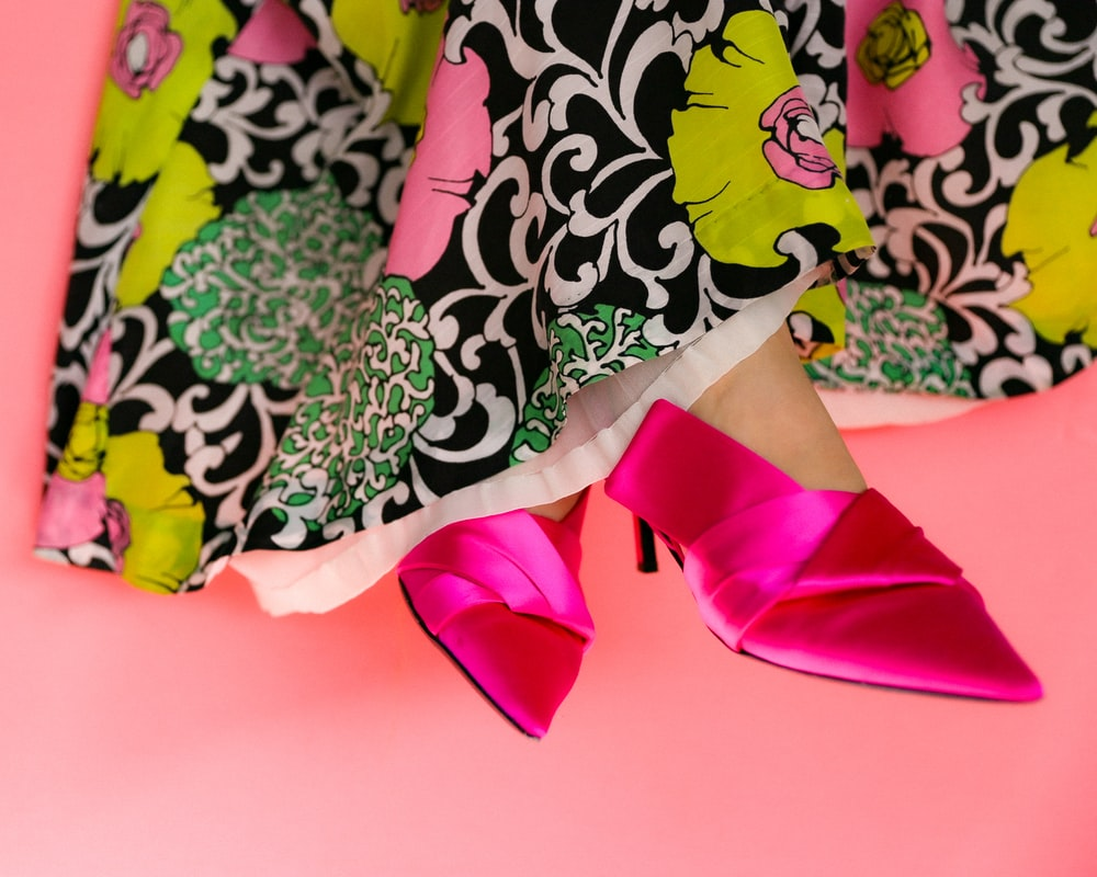 person in pink pants standing on white and green floral textile