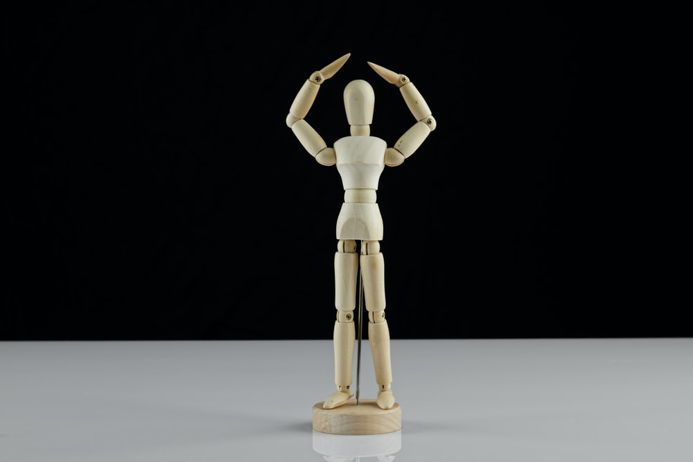 brown wooden human figure on white table
