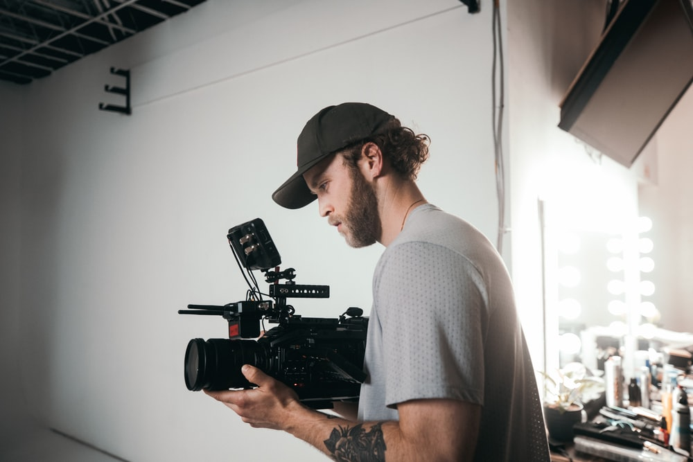 man in gray crew neck t-shirt holding black video camera