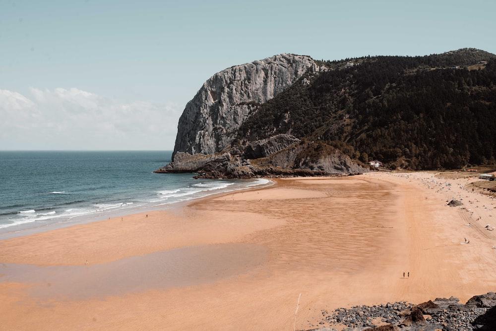brown sand beach near brown rocky mountain under blue sky during daytime