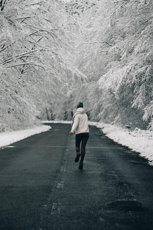 woman in beige coat walking on road