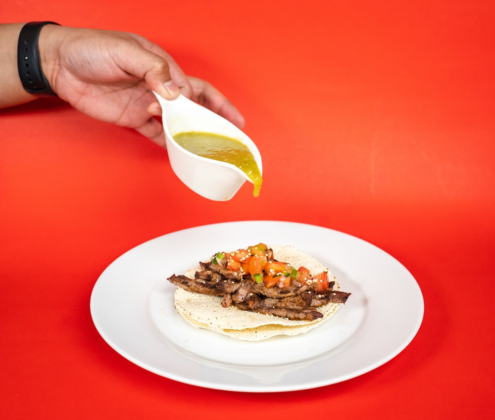 person holding white ceramic plate with sliced lemon