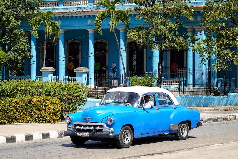 blue and white vintage car parked on roadside during daytime