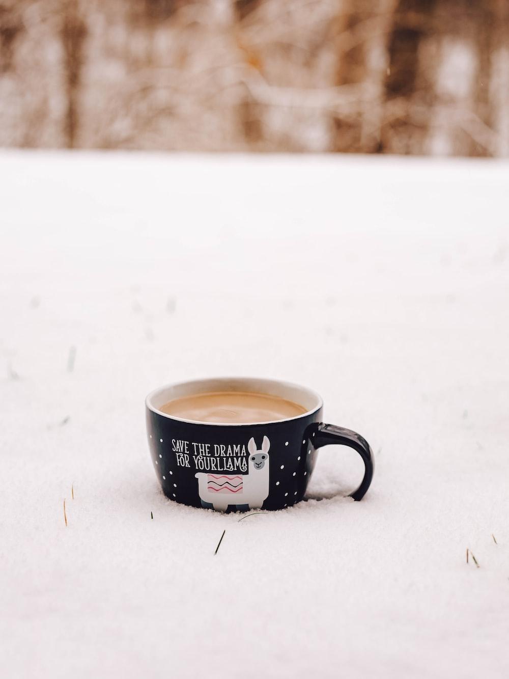 white and black ceramic mug on snow covered ground