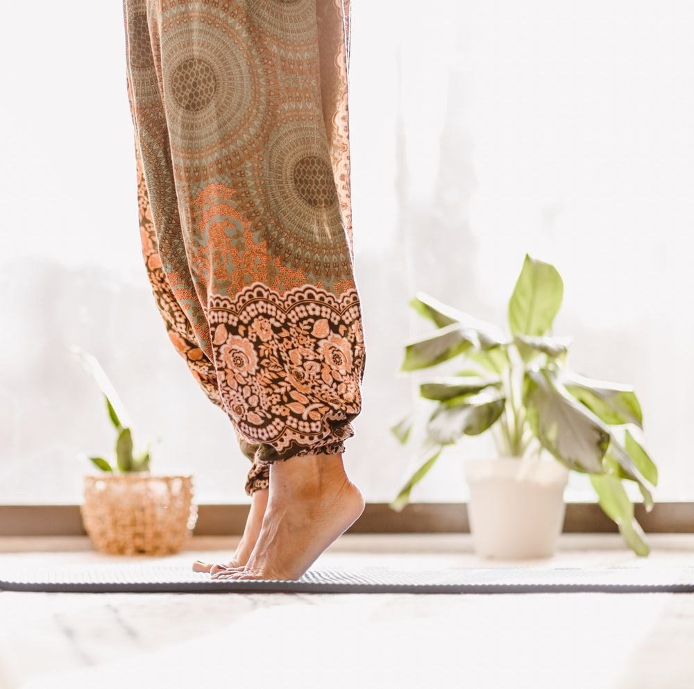 person in brown and beige floral skirt standing on white table