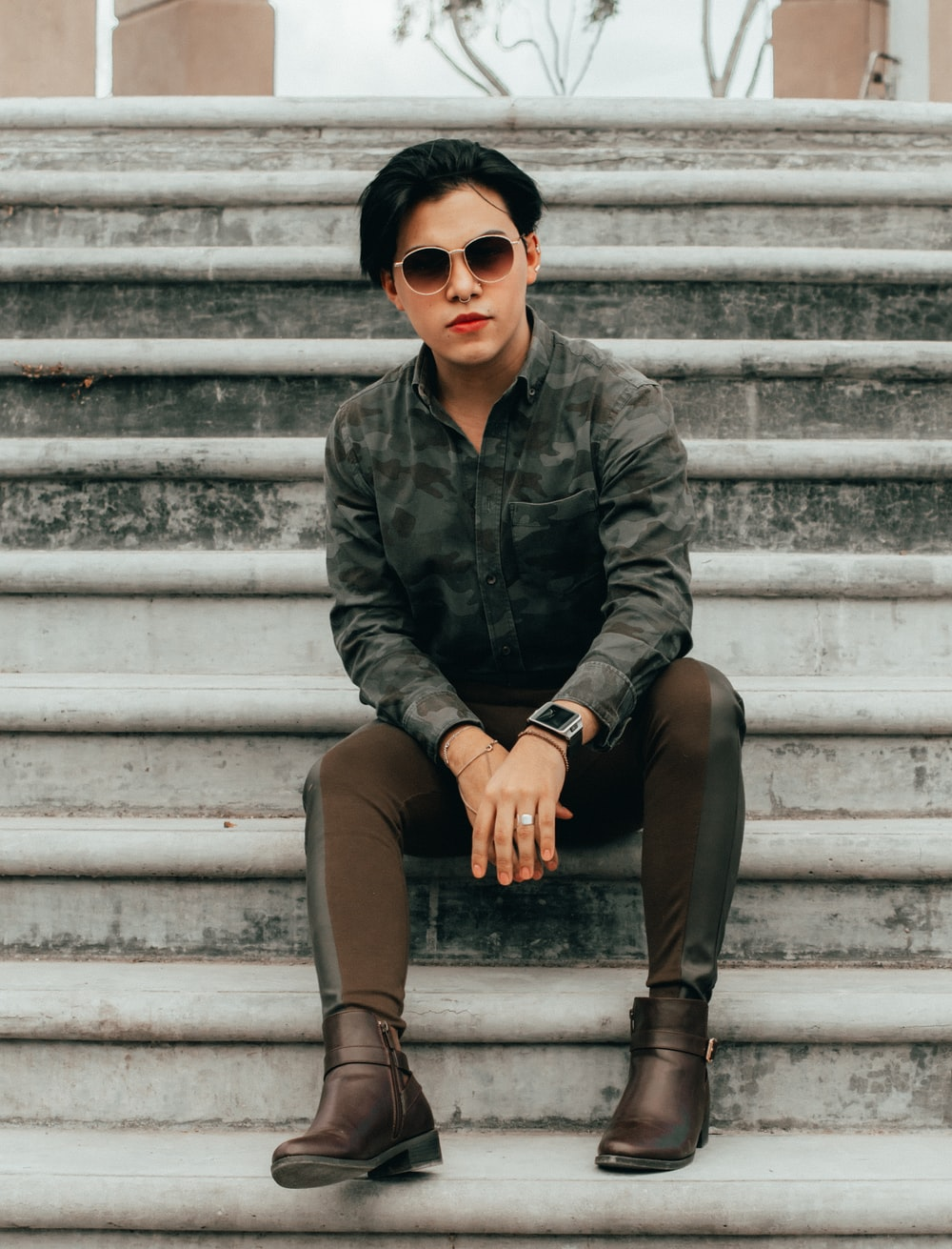 man in black leather jacket and brown pants wearing black sunglasses sitting on white concrete stairs