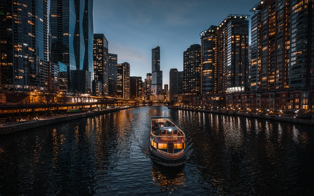 boat on river near city buildings during night time