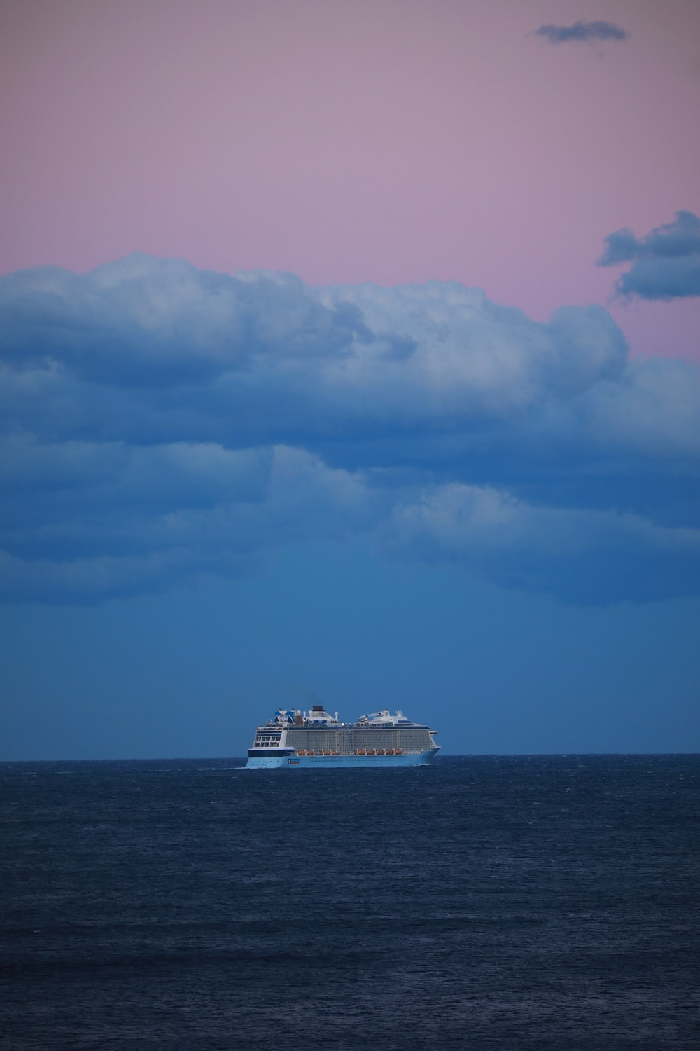 white ship on sea under white clouds