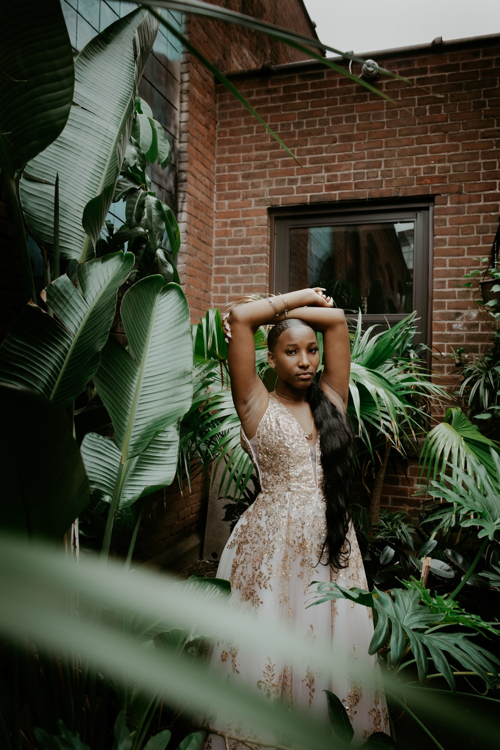 woman in white floral lace dress standing near green plant