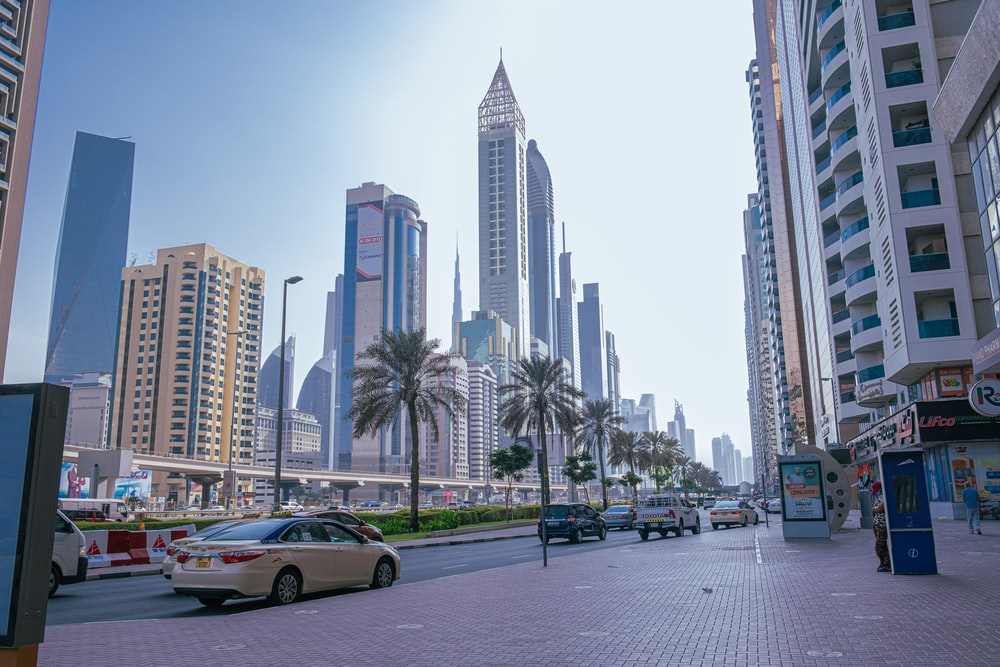 cars on road near high rise buildings during daytime