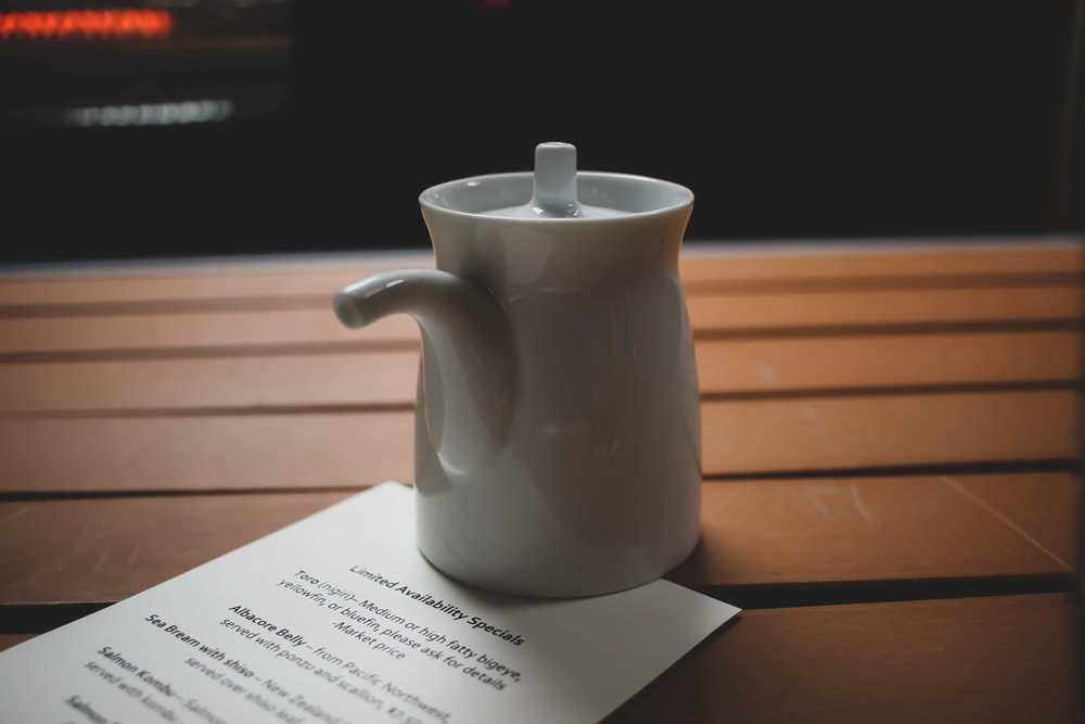 white ceramic teapot on white printer paper