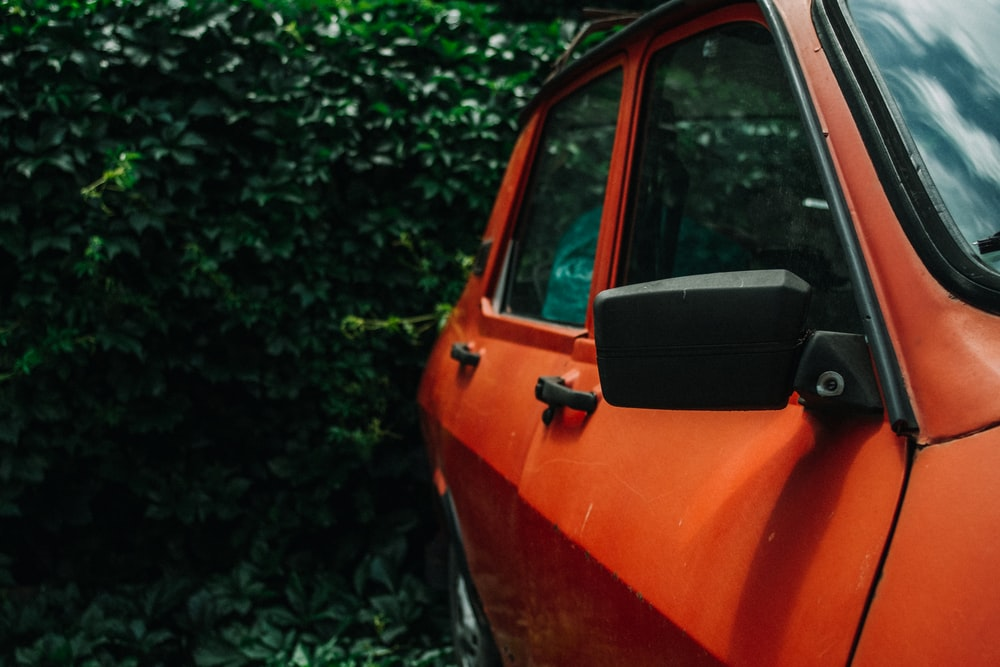 orange car parked near green trees during daytime