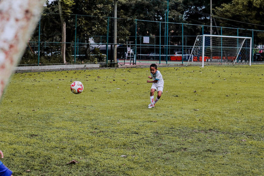 2 boys playing soccer on green grass field during daytime