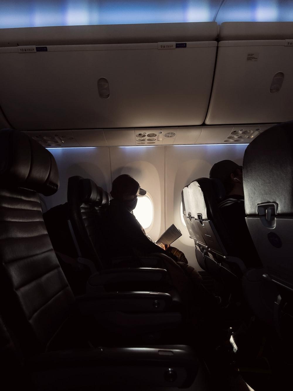 man in black jacket sitting on airplane seat