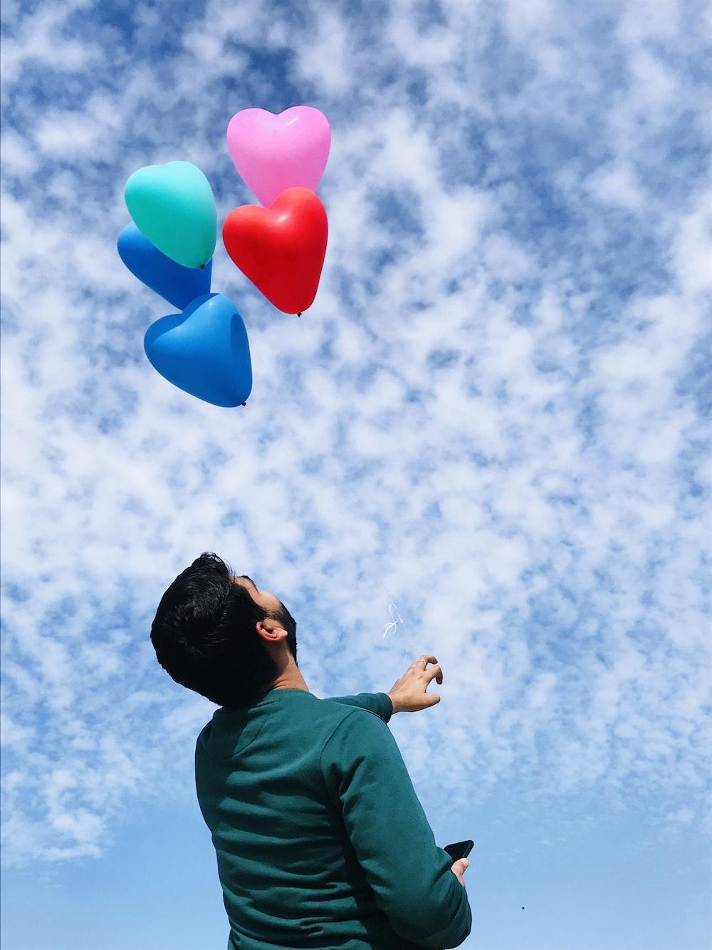 man in green shirt holding blue balloons