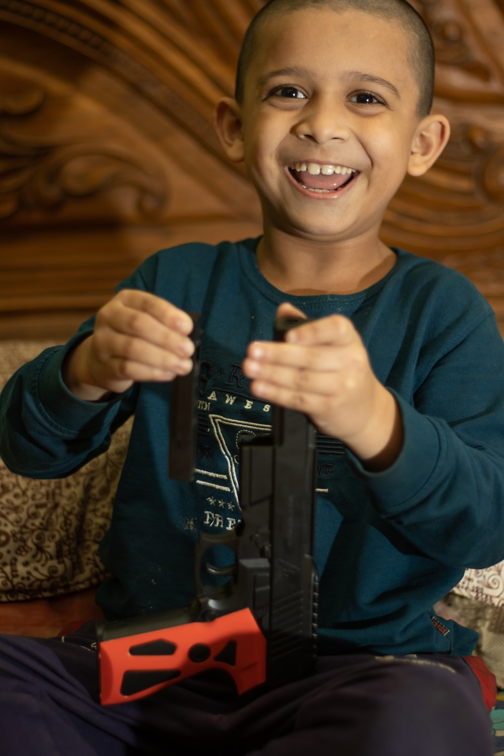 boy in blue sweater holding black rifle toy