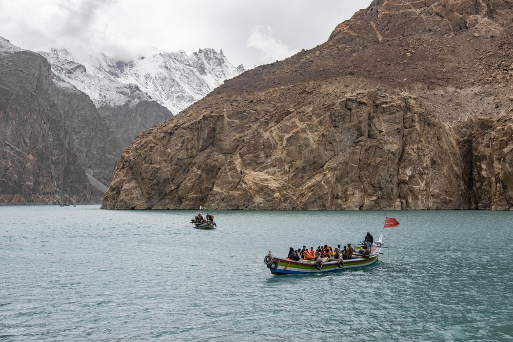 people riding on boat on sea near mountain during daytime