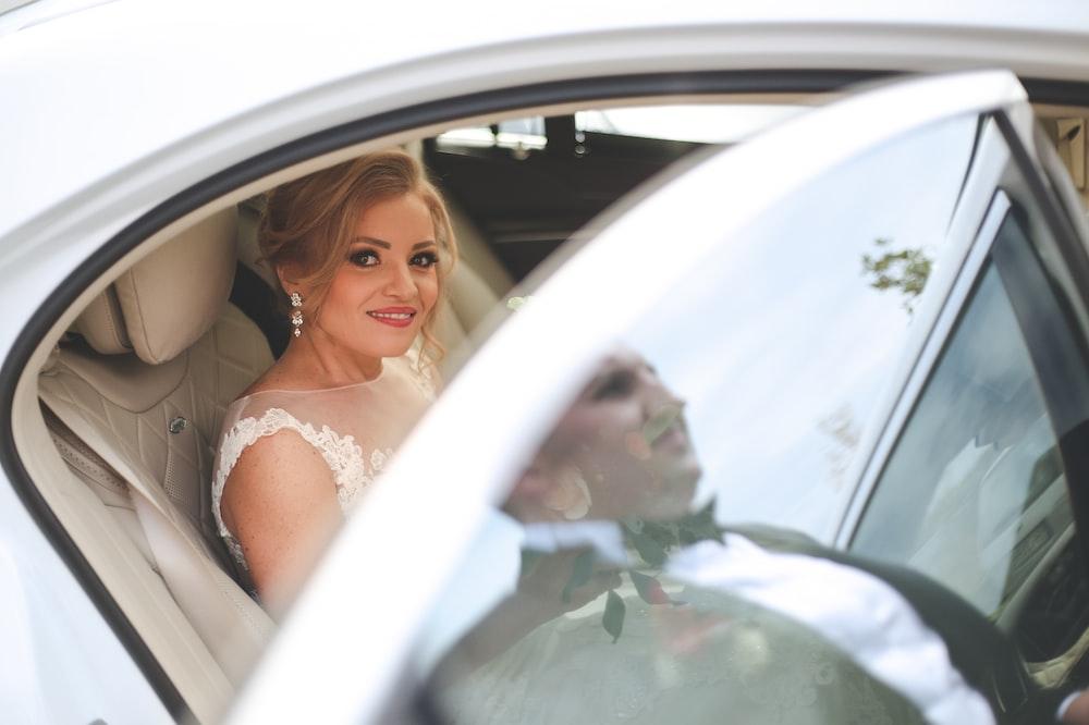 woman in white wedding dress sitting on car seat