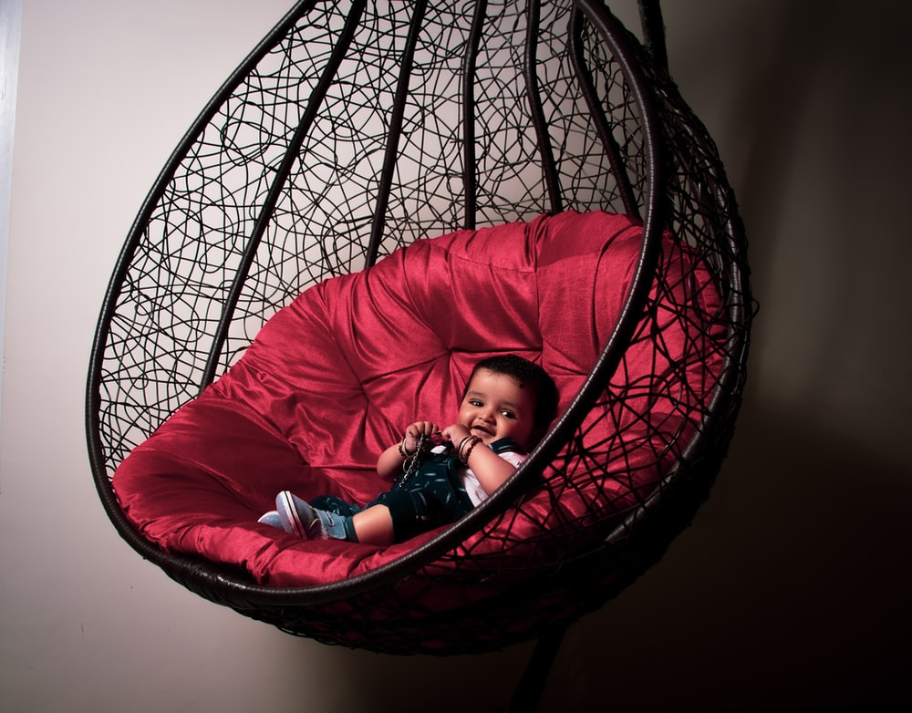 girl in pink jacket lying on red and black hammock