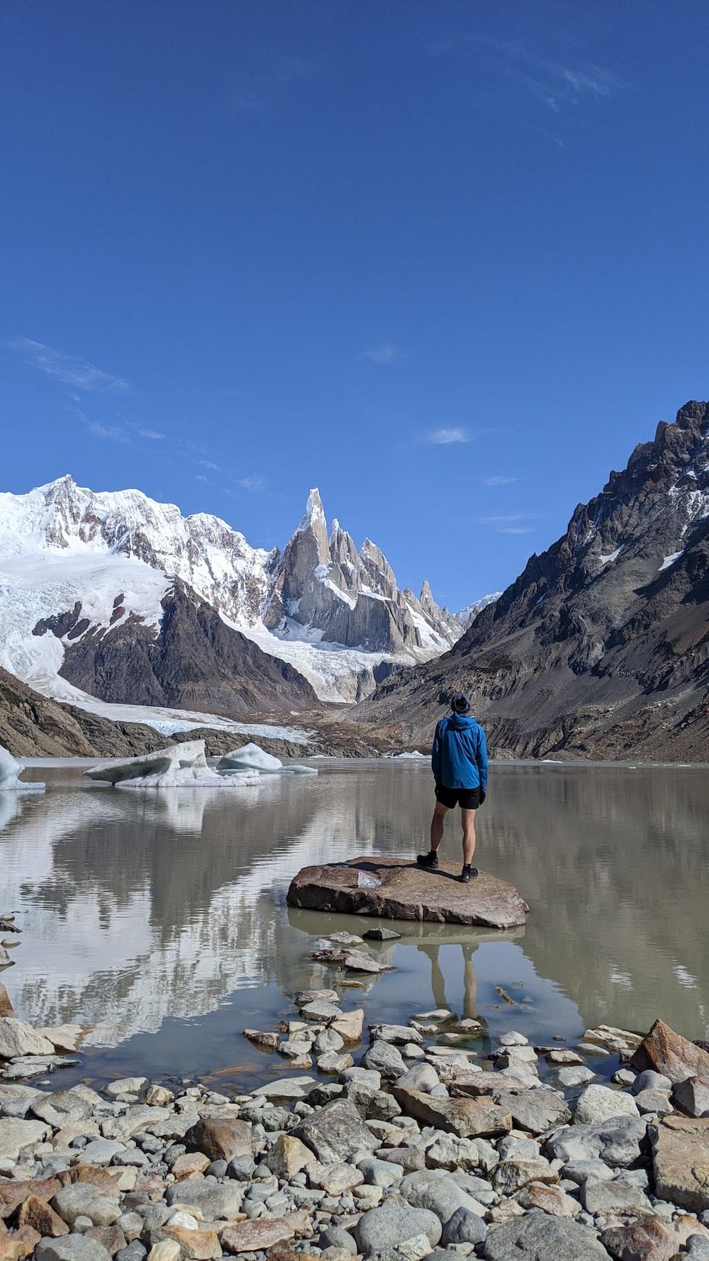 man in blue shirt standing on brown rock near lake during daytime
