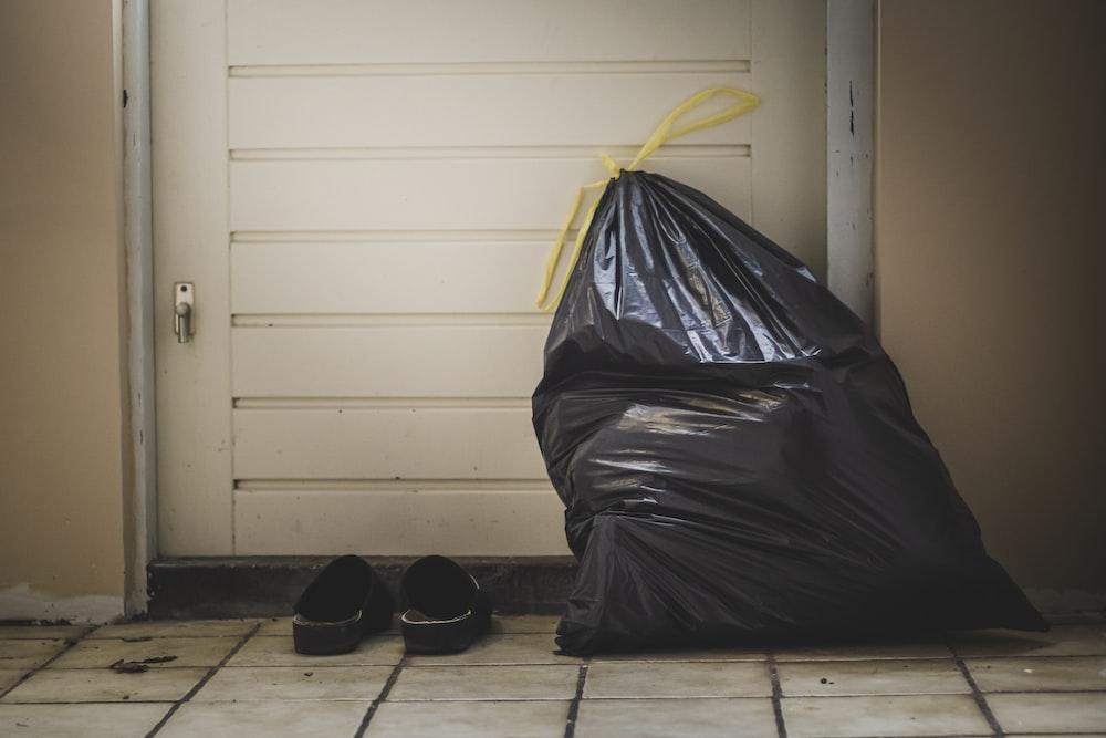 black plastic bag beside white wall