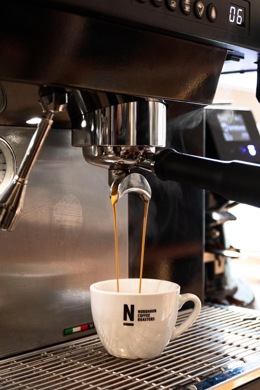 white ceramic mug on silver coffee maker