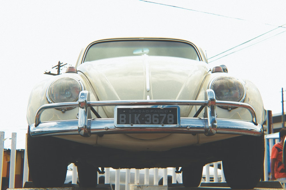 white classic car in a parking lot during daytime