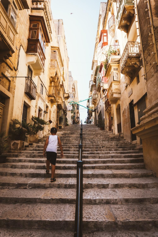 man in white t-shirt walking on gray concrete stairs during daytime