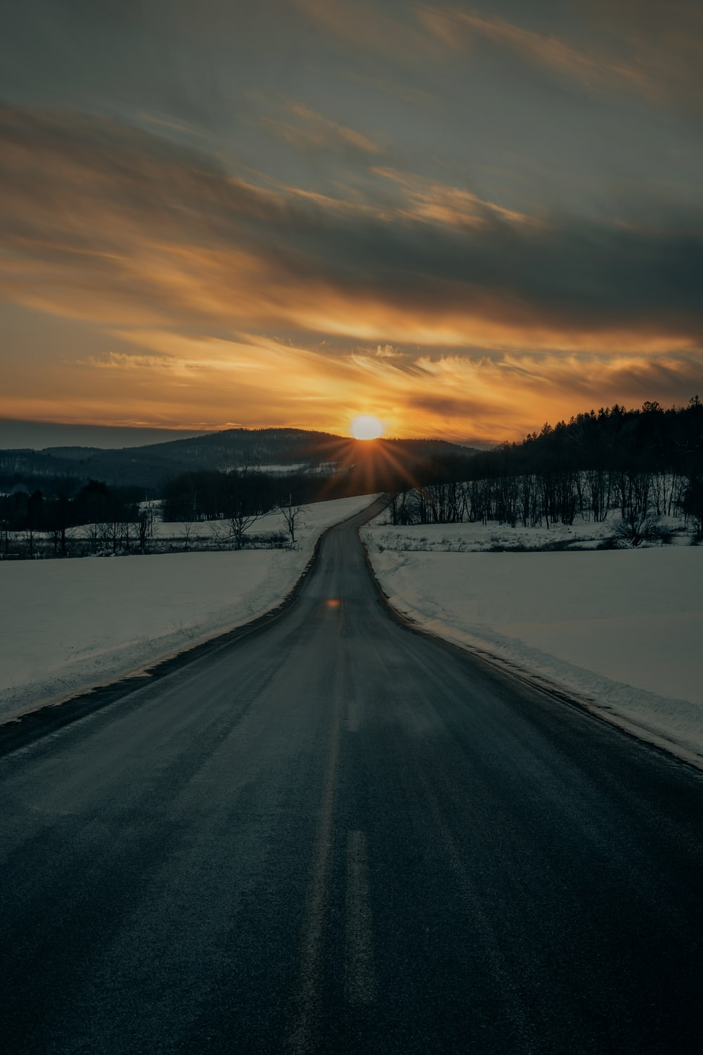 gray concrete road between snow covered ground during sunset