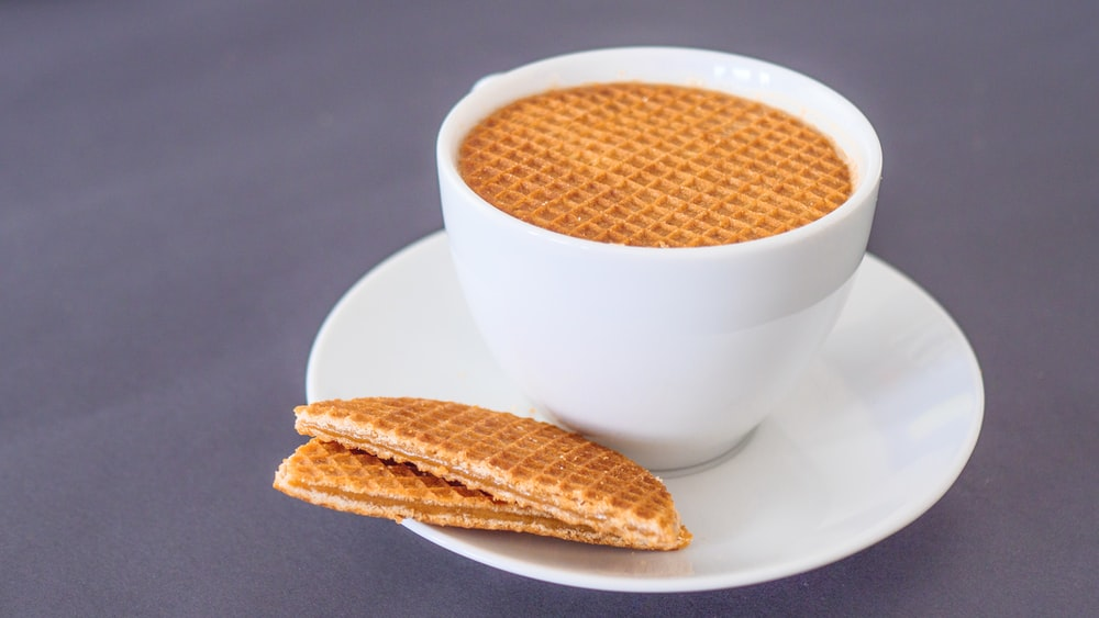 white ceramic teacup with brown liquid