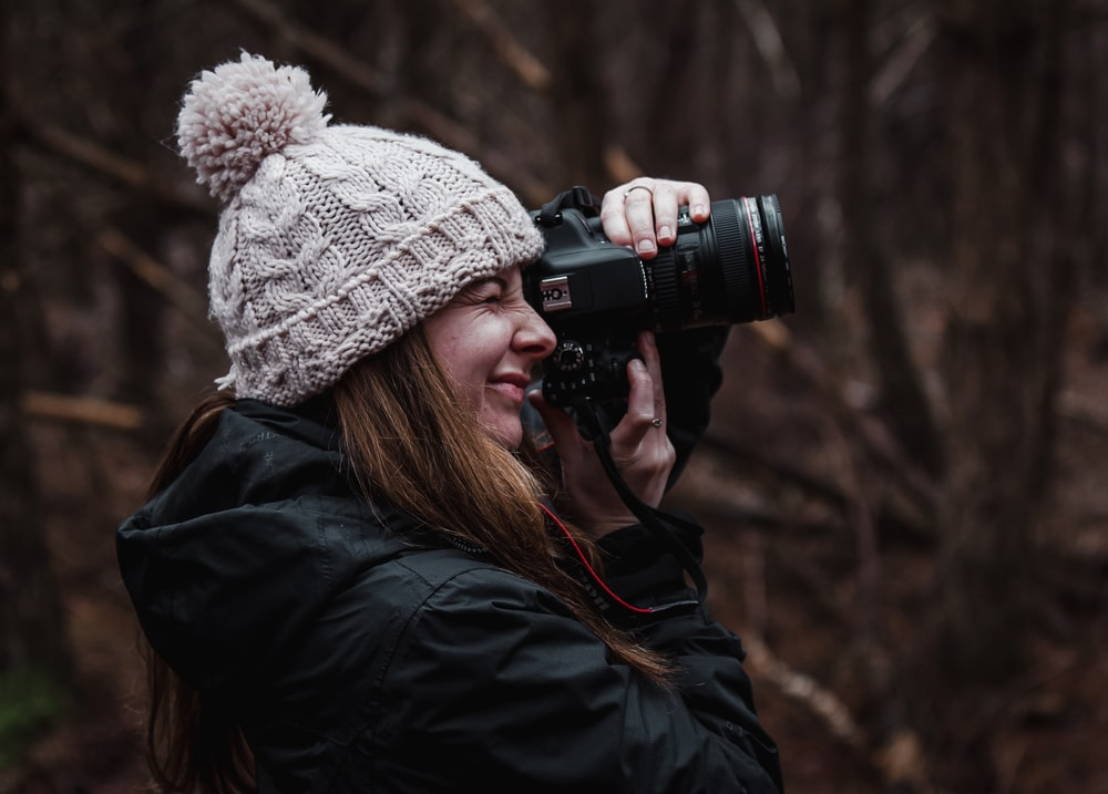 woman in black jacket using black dslr camera