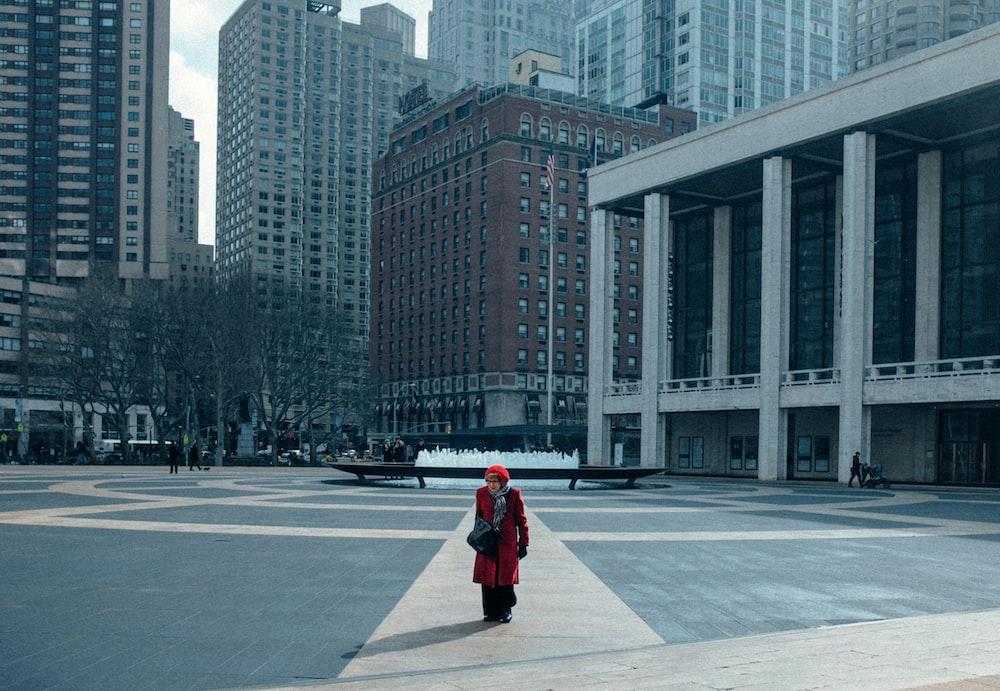 woman in red jacket walking on sidewalk during daytime