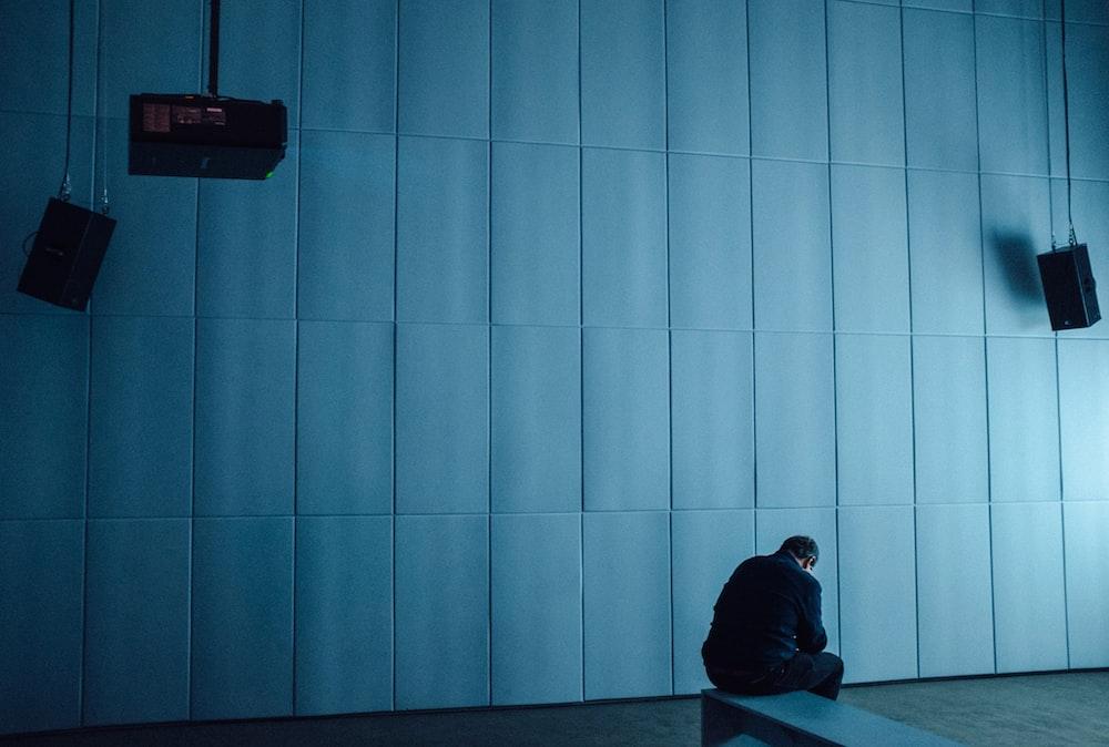 person in black hoodie sitting on floor