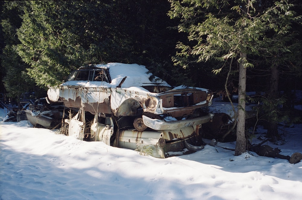 wrecked car on snow covered ground during daytime