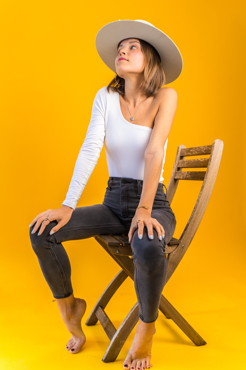 woman in white tank top and black denim jeans sitting on brown wooden chair
