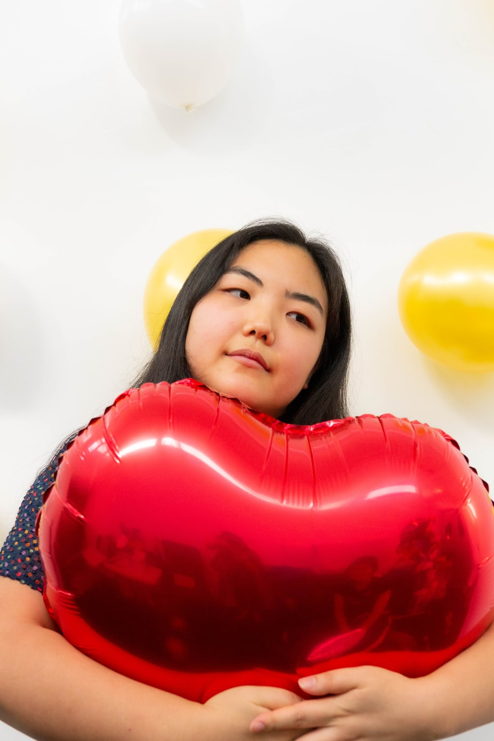 girl in red and white shirt holding heart balloon