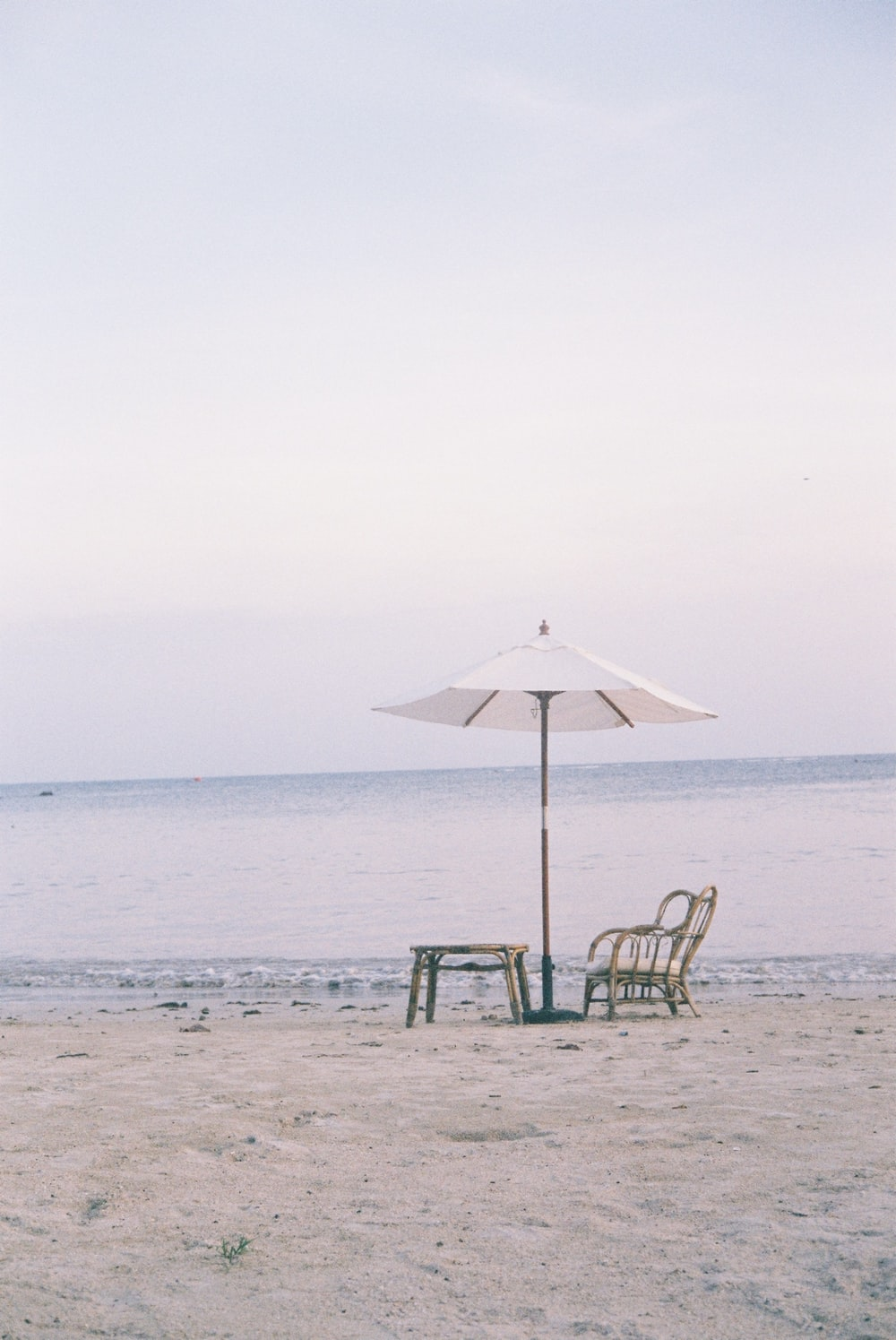 green and black wooden chair under white umbrella on beach during daytime