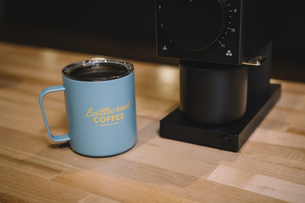 blue ceramic mug on brown wooden table