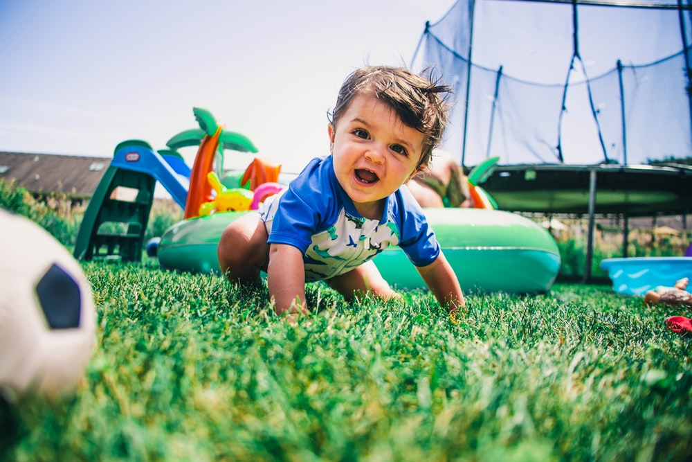 boy in blue and white crew neck t-shirt sitting on green grass field during daytime