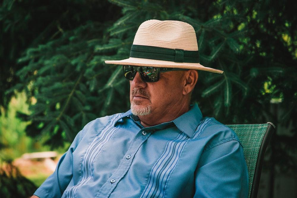 man in blue dress shirt wearing brown fedora hat