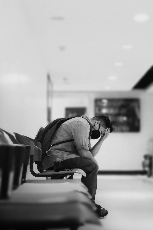 man in black jacket sitting on chair
