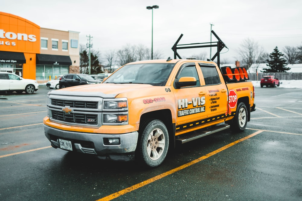 orange chevrolet truck on road during daytime