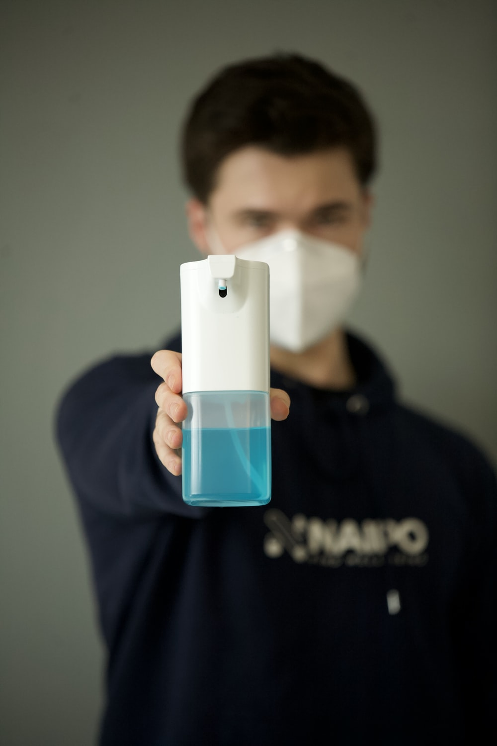 man in black hoodie holding white and blue plastic bottle