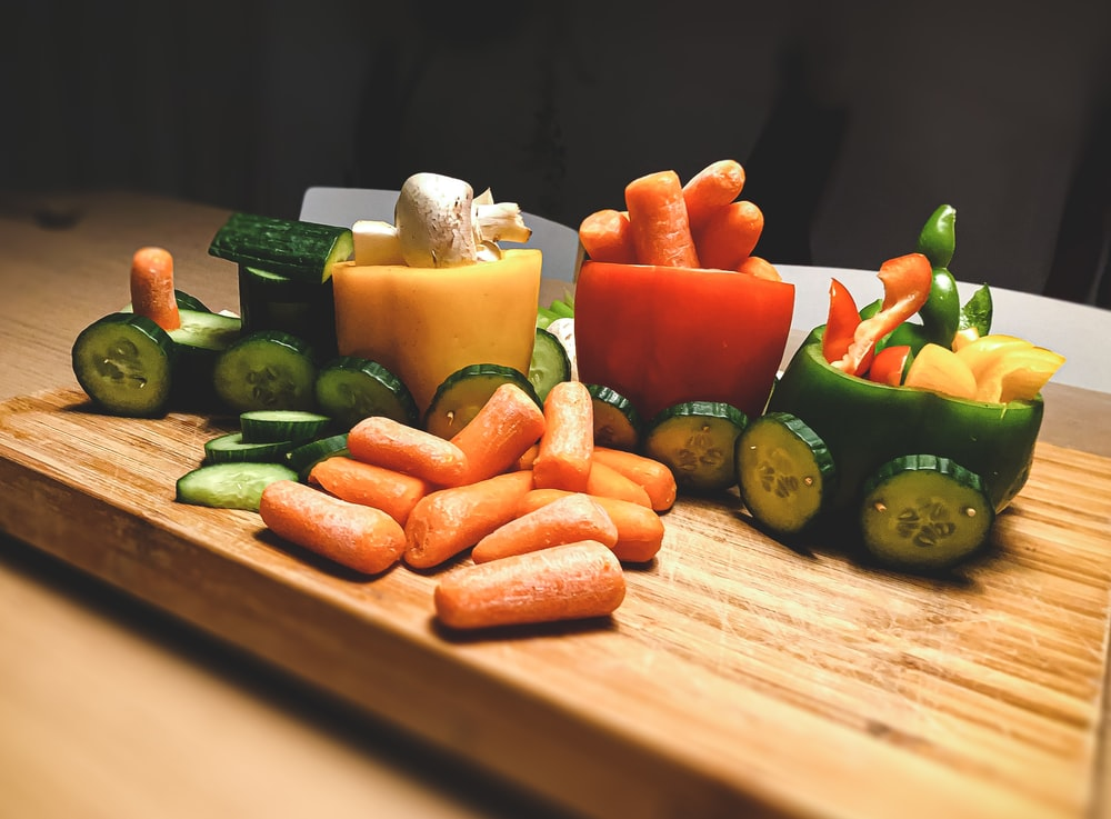 sliced carrots and green bell pepper on brown wooden chopping board