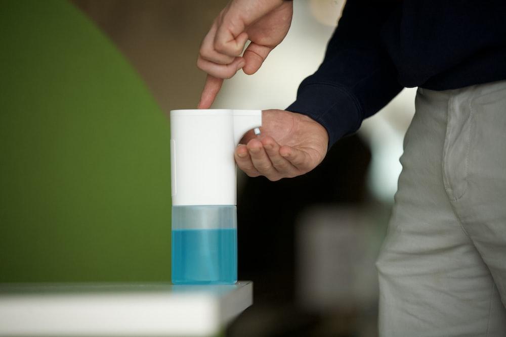 白と青のプラスチックカップを保持している黒の長袖シャツの人